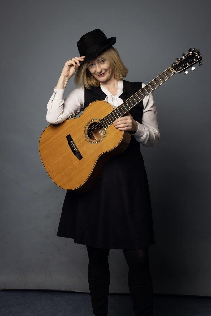 Birgit Glawischnig mit Gitarre und Hut